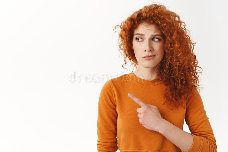 Hesitant worried cute modest redhead curly-haired female, looking pointing left dissatisfied and doubtful, have concern. About bad uncertain choice, standing stock image