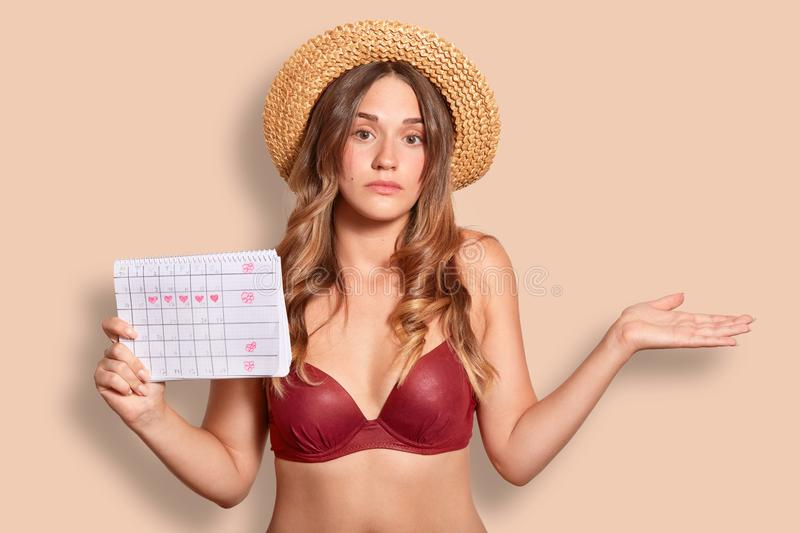 Hesitant young cute female in swimsuit, shruggs shoulders, wears straw hat and bikini, holds period calendar, doesnt know exact da. Te of menstruation, isolated royalty free stock photos