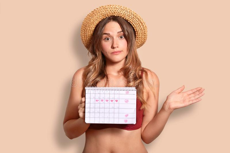 Hesitant young female has vacation abroad, holds period calendar, wonders why she has not regular menstruation, wears stylish stra. W hat, isolated over studio royalty free stock photography