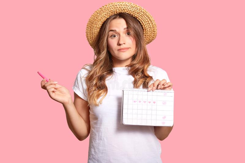 Hesitant young lady carries menstruation period calendar, has clueless expression, wears headgear and white casual t shirt,. Isolated over pink wall, hesitates stock photos