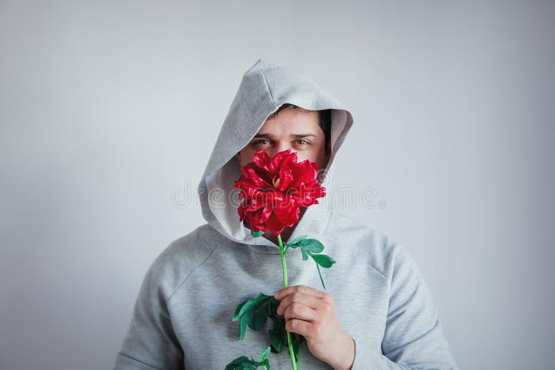 Hesitate man with Peony flower on gray background royalty free stock photos
