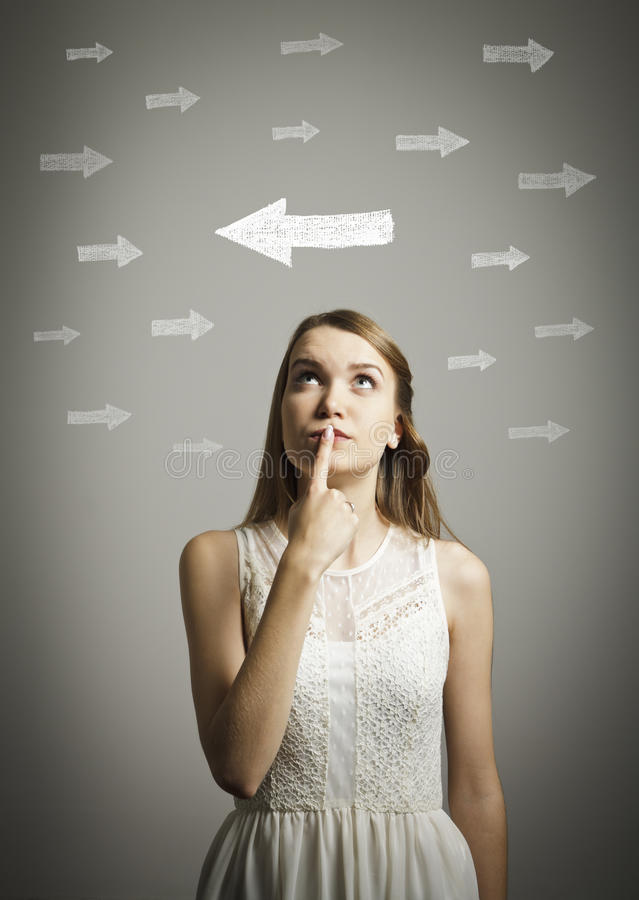 Hesitation. Girl in white and arrows. royalty free stock photography