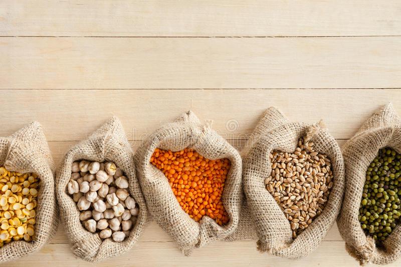 Hessian bags with cereal grains. Peas, chick peas, red lentils, wheat and green mung on wooden table royalty free stock photo