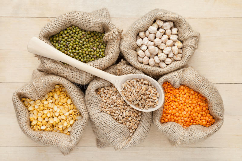 Hessian bags with red lentils, peas, chick peas, wheat and green. Mung on wooden table stock photos