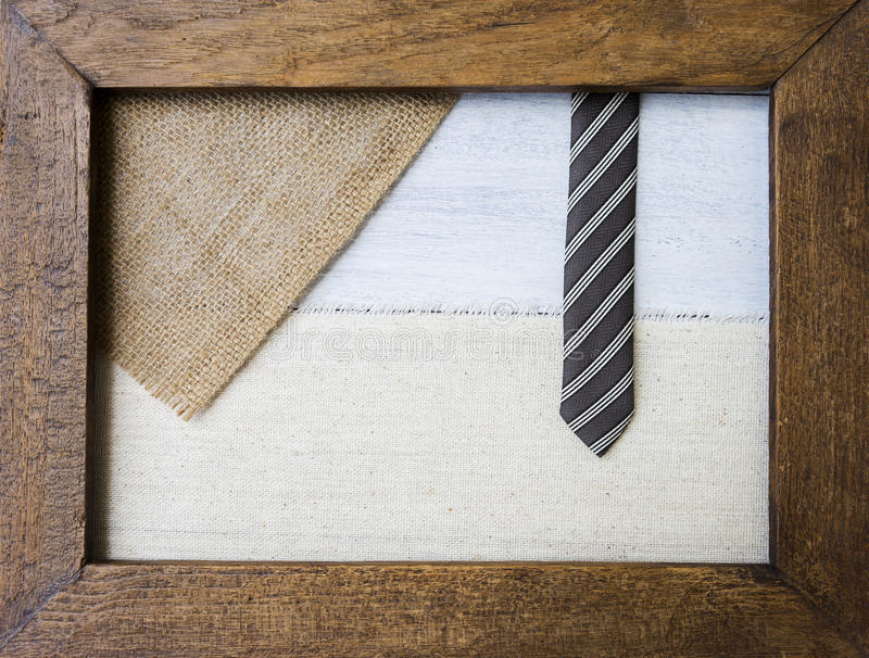 Hessian and canvas with black design necktie in old wooden picture frame. Business and father`s day concept royalty free stock photography