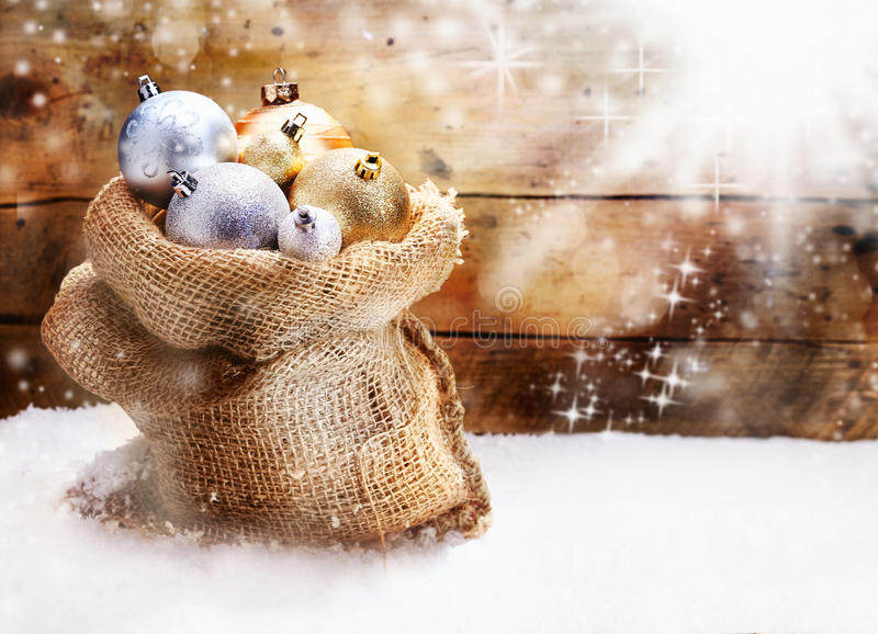 Hessian sack with Christmas baubles. Hessian sack filled to overflowing with gold and silver Christmas baubles resting on snow in front of a rustic wooden wall stock images