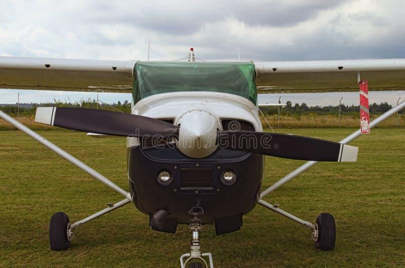 Het één motorvliegtuig bevindt zich op het groene gras in een bewolkte dag Vooraanzicht van vlakte Een klein privé vliegveld in Z stock fotografie