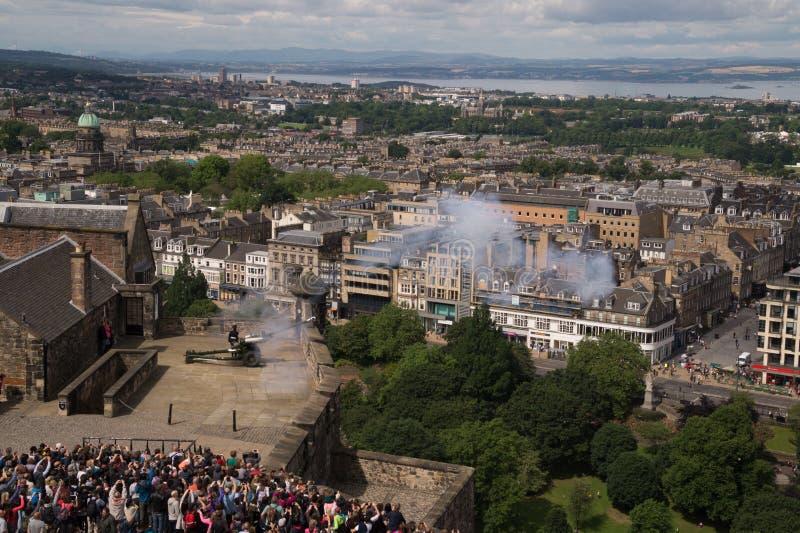 Het Één Uurkanon dat bij het Kasteel van Edinburgh, Schotland in brand wordt gestoken stock afbeeldingen