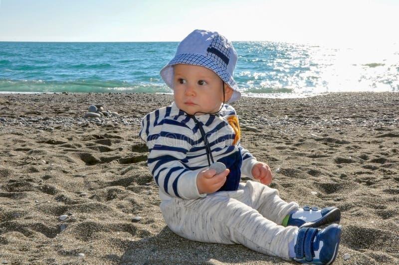 Het éénjarige jonge geitje in een hoedenzitting op het strand stock foto's