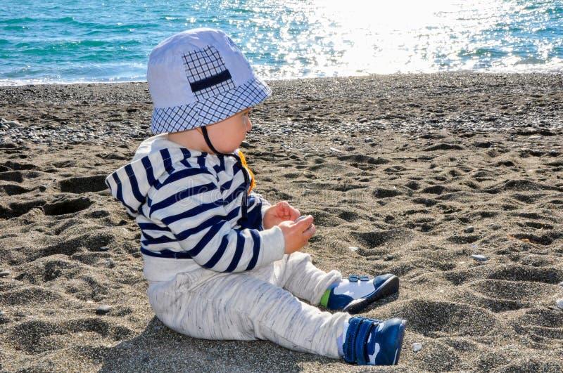 Het éénjarige jonge geitje in een hoedenzitting op het strand stock fotografie