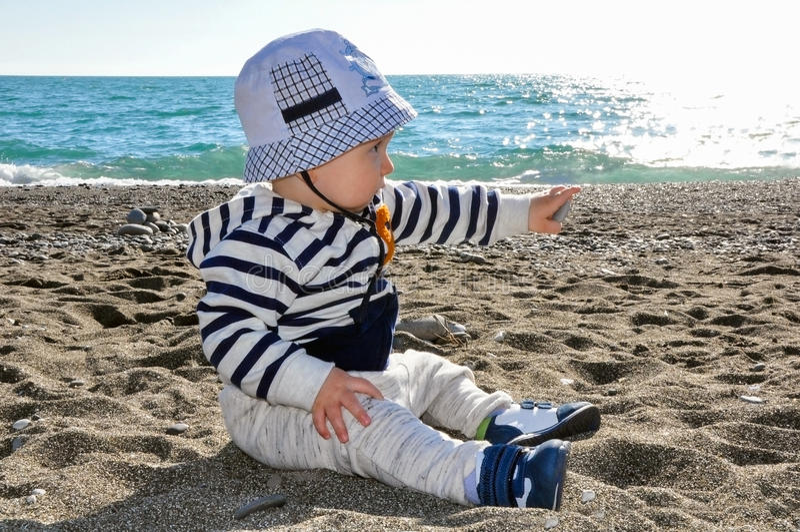 Het éénjarige jonge geitje in een hoedenzitting op het strand royalty-vrije stock afbeeldingen