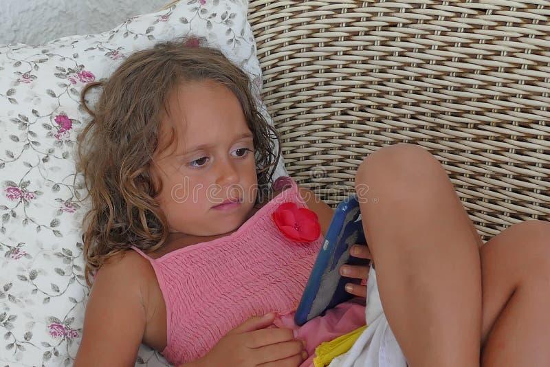 het 4 éénjarigenmeisje bekijkt met concentratie mobiel stock afbeeldingen