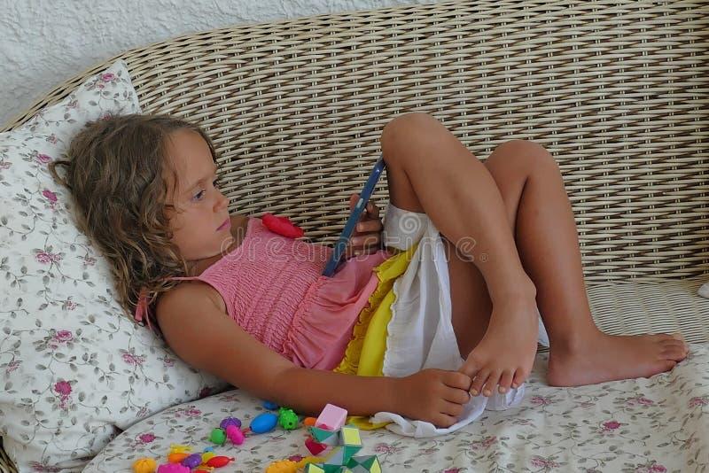 het 4 éénjarigenmeisje bekijkt met concentratie mobiel stock afbeelding