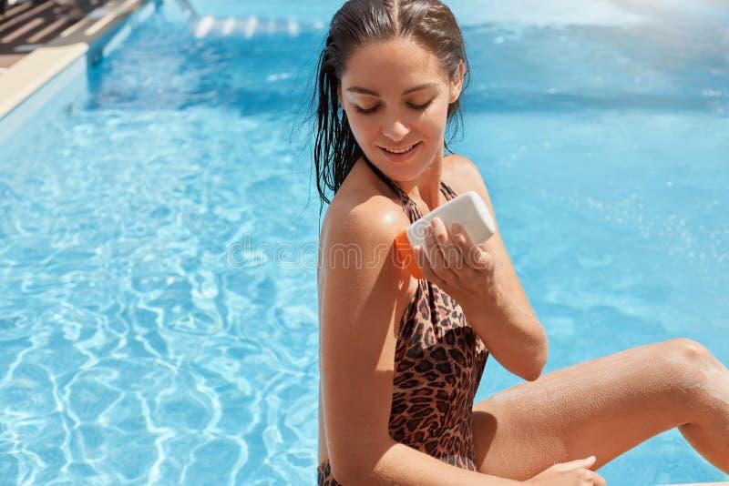 Het aanbiddelijke aantrekkelijke vrouwelijke stellen over zwembadachtergrond, bekijkend haar huid, die huidprocedures hebben, die royalty-vrije stock afbeeldingen