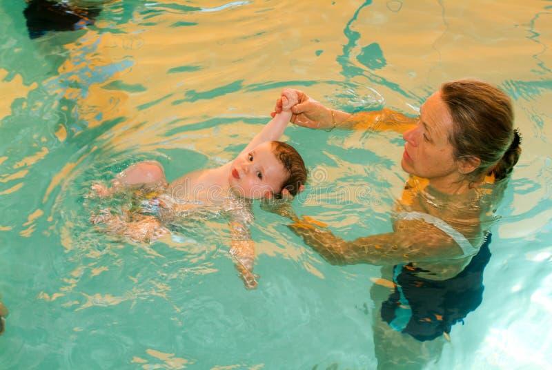 Het aanbiddelijke baby genieten die in een pool met zijn moeder zwemmen royalty-vrije stock foto's