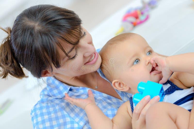 Het aanbiddelijke baby spelen met babysitter royalty-vrije stock foto's