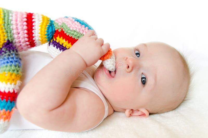 Het aanbiddelijke baby spelen met kleurrijke gemaakte hand - haak stuk speelgoed royalty-vrije stock foto
