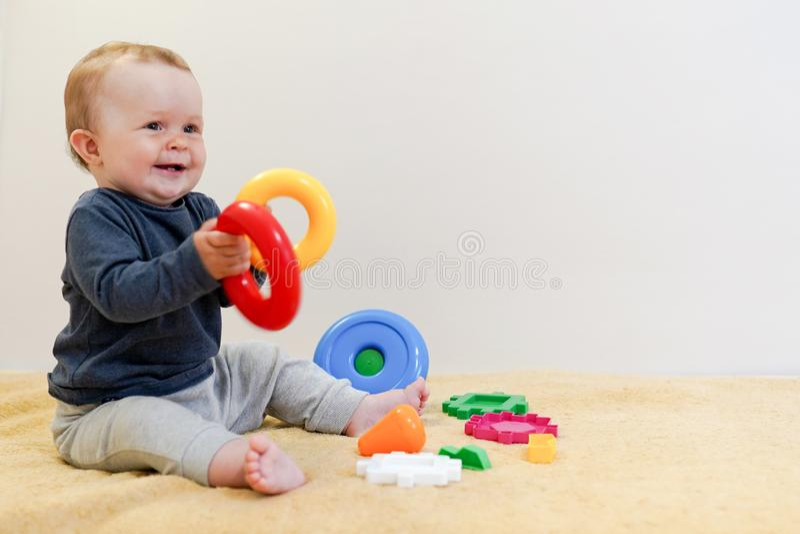 Het aanbiddelijke baby spelen met onderwijsspeelgoed Achtergrond met exemplaarruimte Gelukkig gezond kind die pret hebben thuis v royalty-vrije stock afbeeldingen