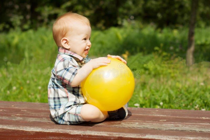 Het aanbiddelijke babyjongen spelen met een gele strandbal royalty-vrije stock afbeeldingen
