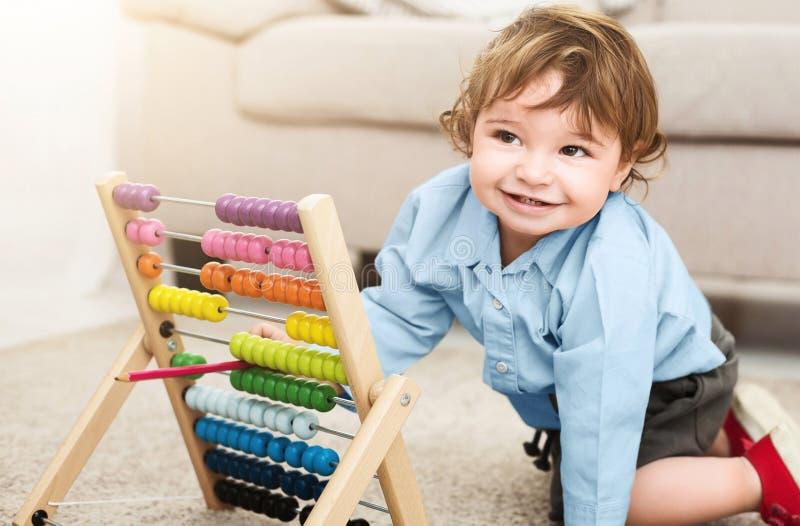 Het aanbiddelijke babyjongen spelen met kleurrijke scores thuis royalty-vrije stock foto's