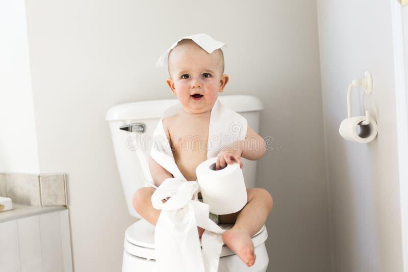 Het aanbiddelijke babyjongen spelen met toiletpapier stock fotografie