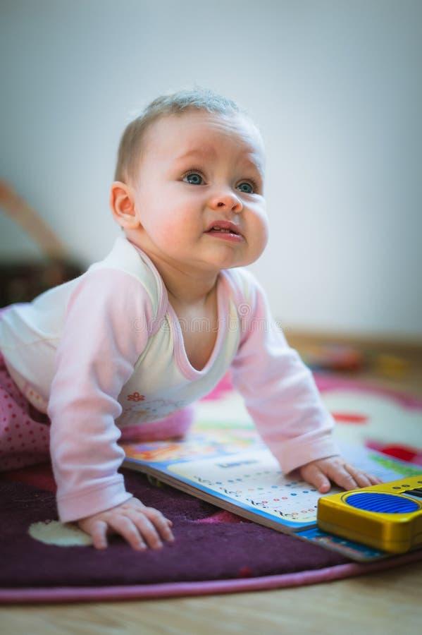 Het aanbiddelijke babymeisje kruipt op al foursvloer bij stock afbeelding