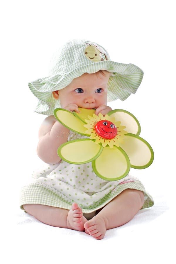 Het aanbiddelijke babymeisje proeft haar stuk speelgoed bloem stock afbeelding