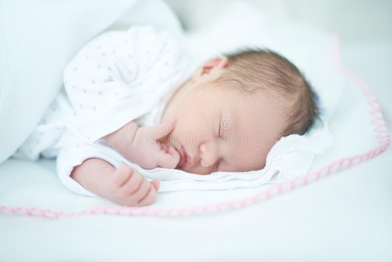 Het aanbiddelijke Babymeisje slaapt op Bed stock afbeelding