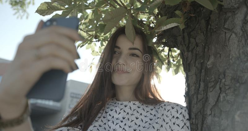 Het aanbiddelijke brunette glimlacht en neemt selfie op de mobiele telefoon in zonnestralen in park 4k lengte royalty-vrije stock foto's