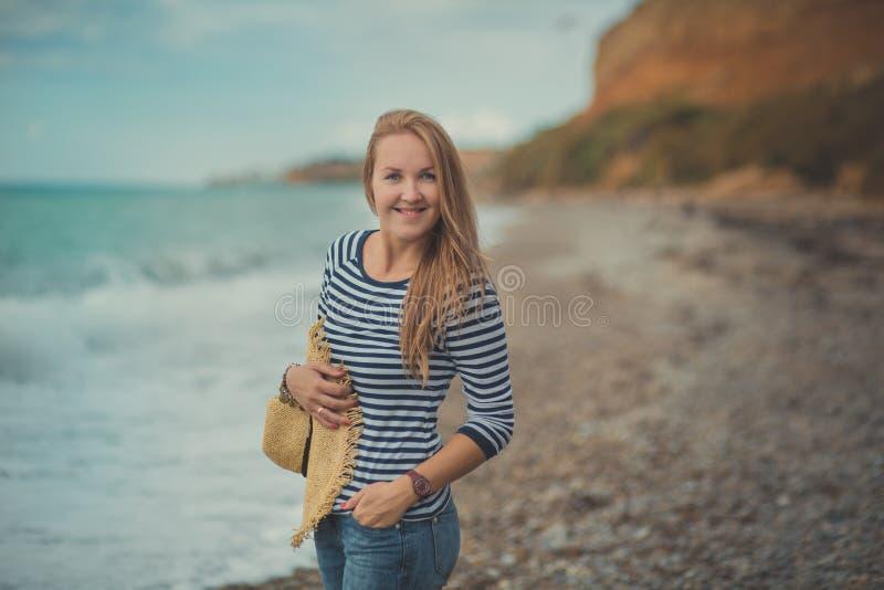 Het aanbiddelijke de vrouwenvooravond van de schoonheidsdame het lopen stellen alleen op strand overzeese zij oceaanvakantie die  stock fotografie
