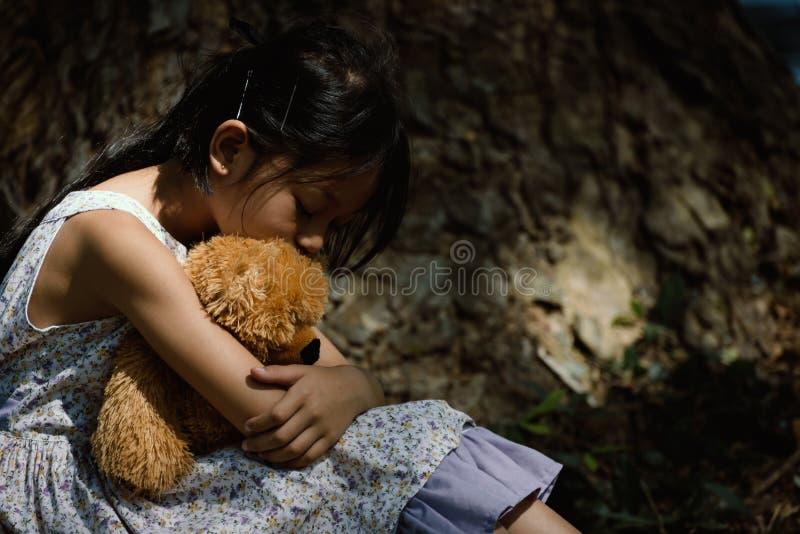 Het aanbiddelijke droevige meisje met teddybeer in park, Meisje is huggin stock afbeeldingen