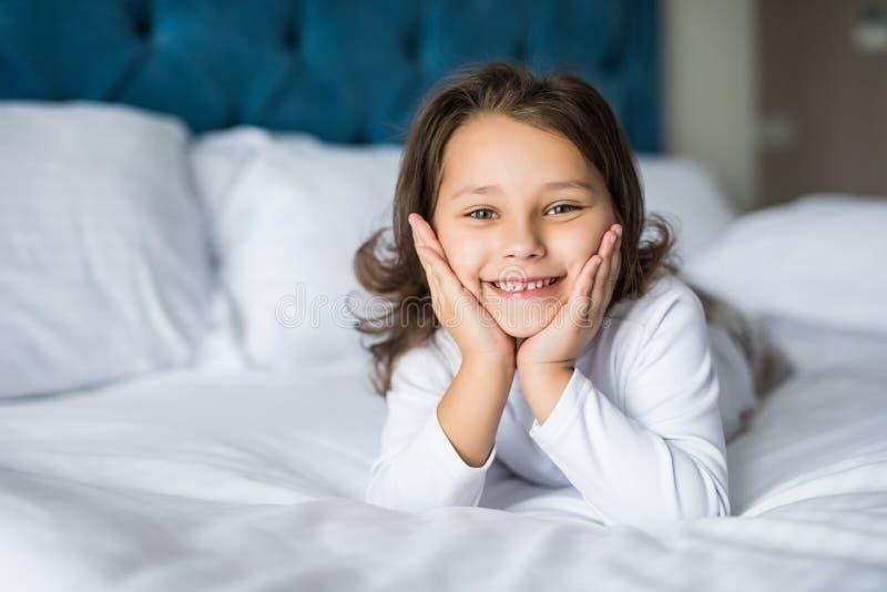 Het aanbiddelijke glimlachende meisje met glimlach waked omhoog in haar bed stock fotografie