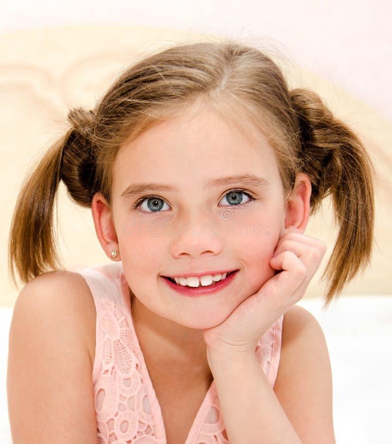 Het aanbiddelijke glimlachende meisje rust op een bed royalty-vrije stock fotografie