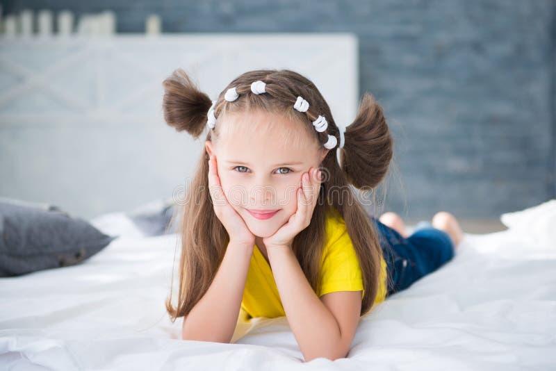 Het aanbiddelijke glimlachende meisje waked omhoog in haar bed stock foto