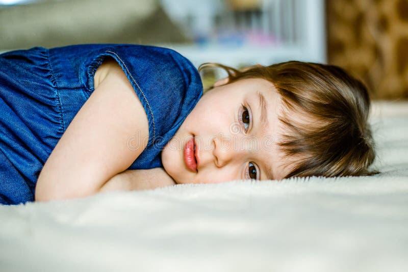 Het aanbiddelijke glimlachende meisje waked omhoog in haar bed royalty-vrije stock afbeeldingen