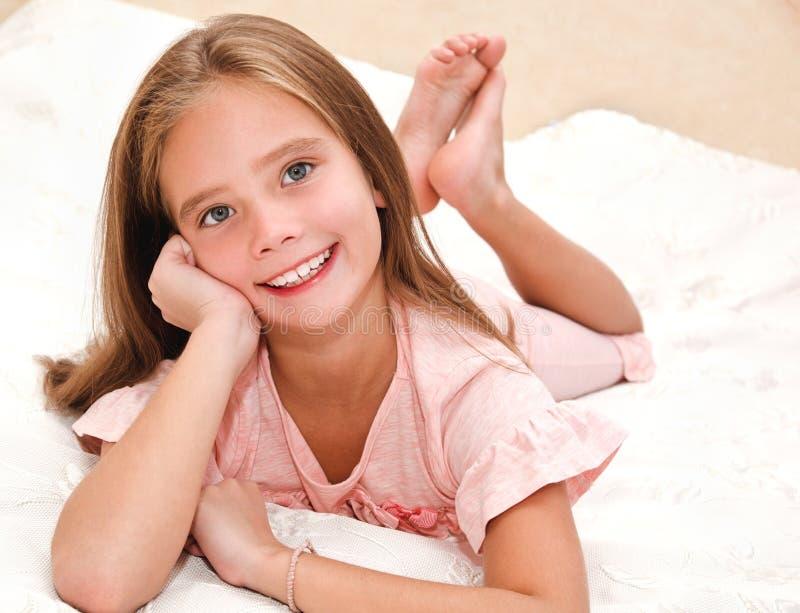 Het aanbiddelijke glimlachende meisjekind rust op een bed royalty-vrije stock foto's