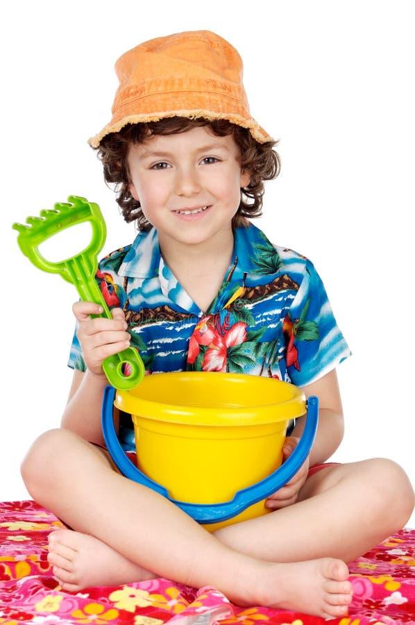 Het aanbiddelijke jongen spelen in het strand stock afbeelding