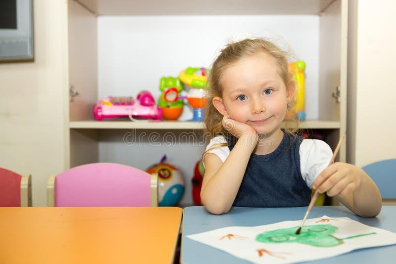 Het aanbiddelijke kindmeisje trekt een borstel en verven in kinderdagverblijfruimte Jong geitje in kleuterschool in de peuterklas stock afbeelding