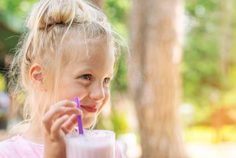 Het aanbiddelijke leuke portret die van het kleuter Kaukasische blonde meisje verse smakelijke aardbeimilkshake in openlucht nipp royalty-vrije stock foto