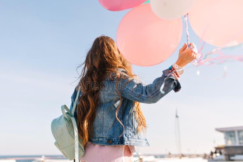Het aanbiddelijke meisje die retro jasje dragen die zich op de dijk bevinden en bewondert de hemel na haar verjaardagspartij Jong stock afbeelding
