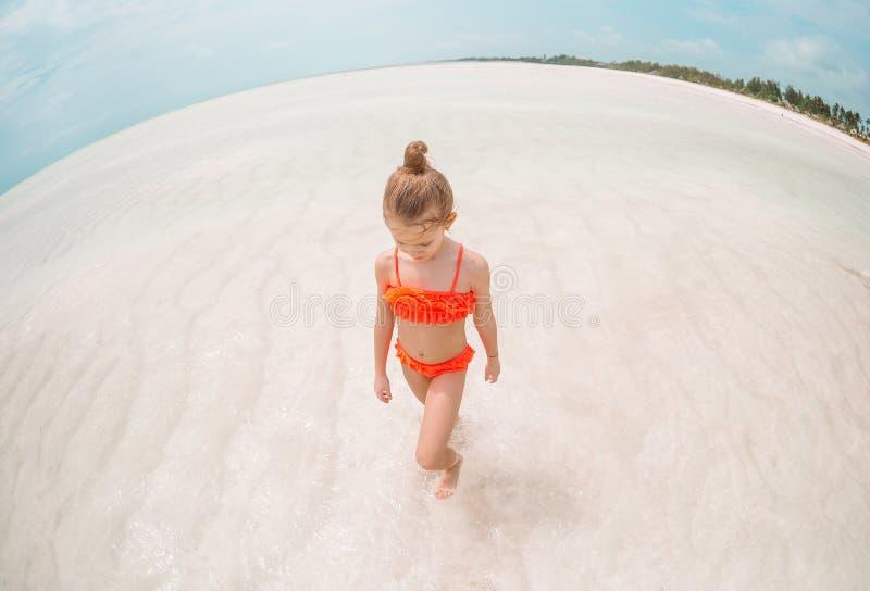 Het aanbiddelijke meisje heeft pret bij tropisch strand tijdens vakantie stock afbeelding