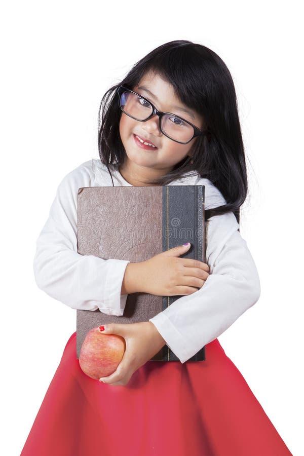Het aanbiddelijke meisje houdt een boek en een appel in studio stock afbeelding