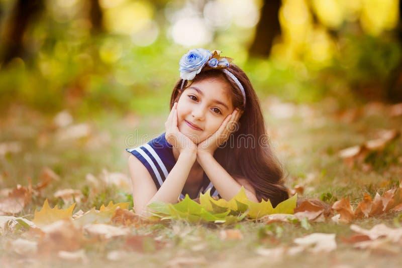 Het aanbiddelijke meisje met gele bladeren ligt royalty-vrije stock foto's