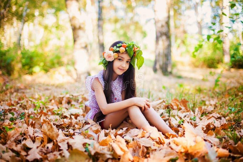 Het aanbiddelijke meisje met gele bladeren zit stock fotografie