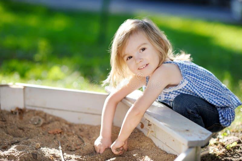 Het aanbiddelijke meisje spelen in een zandbak stock foto