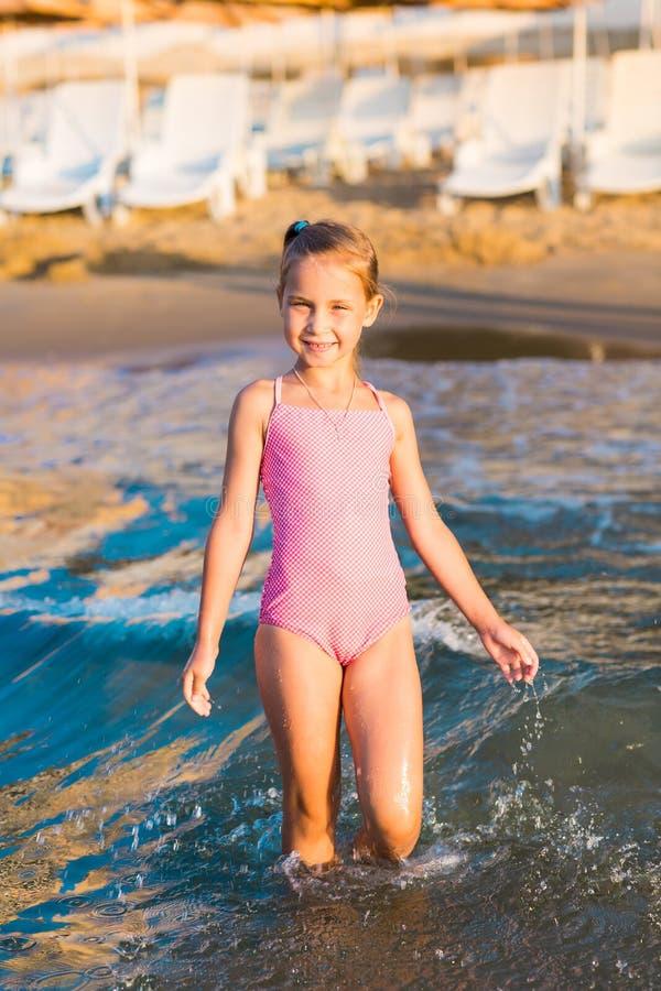 Het aanbiddelijke meisje spelen in het overzees op een strand royalty-vrije stock foto