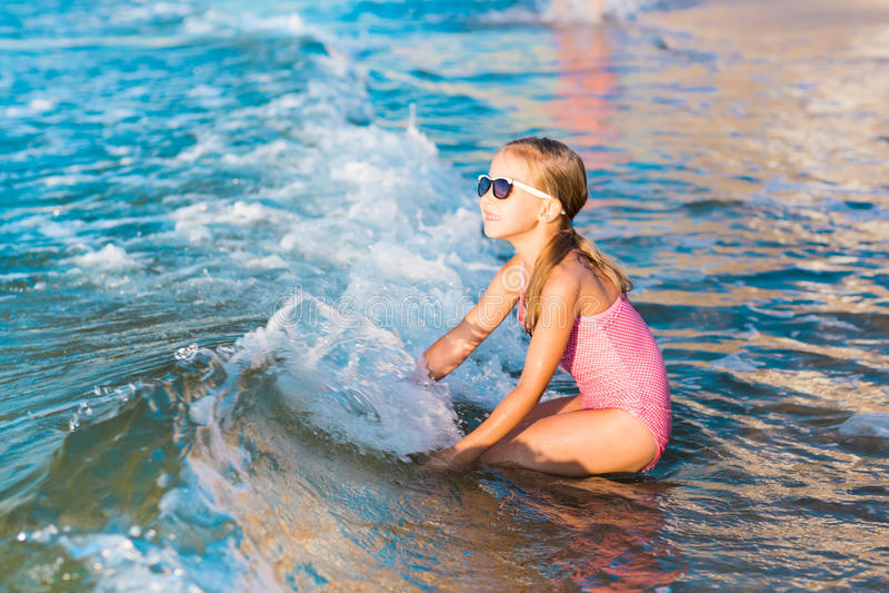 Het aanbiddelijke meisje spelen in het overzees op een strand royalty-vrije stock afbeelding