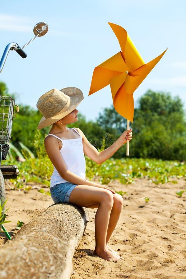 Het aanbiddelijke meisje spelen met document windmolen royalty-vrije stock afbeeldingen