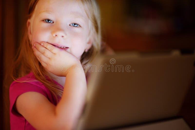 Het aanbiddelijke meisje spelen met een digitale tablet in een donkere ruimte royalty-vrije stock fotografie