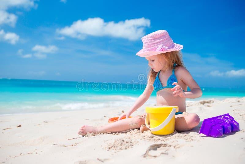 Het aanbiddelijke meisje spelen met strandspeelgoed op wit zandig strand stock afbeelding